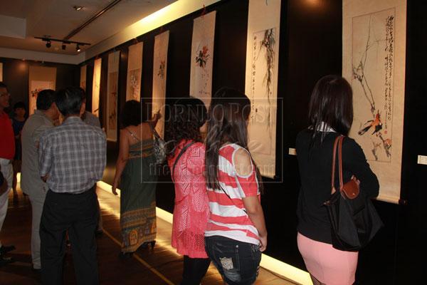 IMPRESSIVE: Visitors admiring Chin's art work.