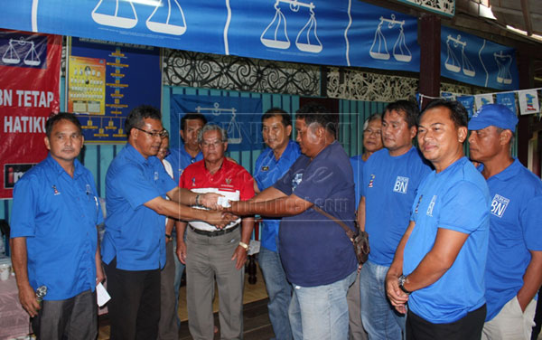 USE IT WELL: Nyabong (second left) hands over donation to a representative of fire victims of Uma Kulit whose 14-door longhouse was burnt last month as Ugak (fifth left) and others look on.