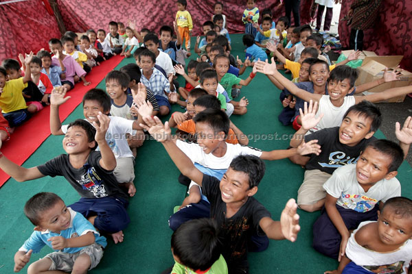 HAVING FUN: Children evacuated from Kampung Sungai Merah having a great time at Cenderawasih Civic Centre which serves as their temporary home near Felda Sahabat oil palm plantation. — Bernama photo