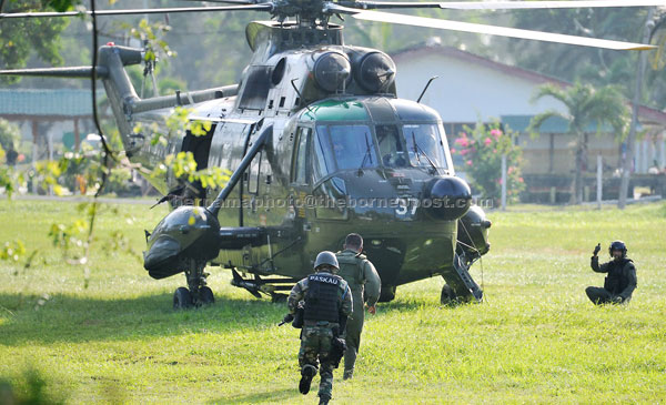 OFF TO THE FRONTLINE: Armed Forces commandos board a Nuri helicopter for deployment to Kampung Tanduo for the offensive.  — Bernama photo