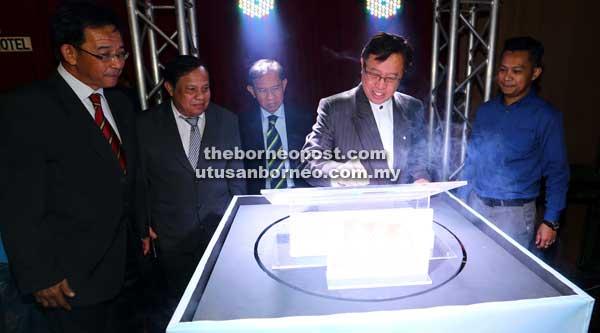 SIMBOLIK: Abang Johari menandatangani plak logo Skim Pinjaman Perumahan Mutiara sebagai simbolik pelancaran sambil disaksikan Abdul Karim (kiri), Ahmad Tarmizi (tiga kiri) serta tetamu jemputan lain.