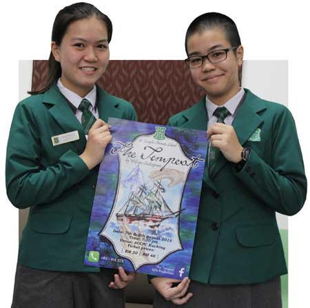 Production manager Ashley Yap May Yee (left) and director Cheryl Ann Teng Sze Yi holding a poster for their school play — The Tempest.