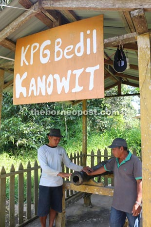 Lalip Sagon (left) and Geeman showing the cannon presented to the village by the Brookes.