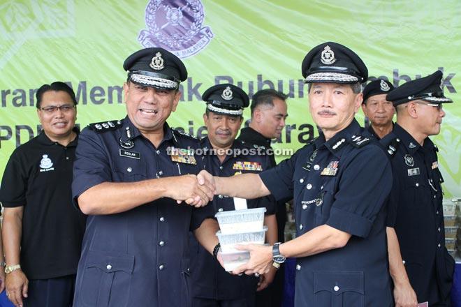 Gan (right) symbolically presents the Bubur Lambuk to Kuching police chief ACP Roslan Bek Ahmad.