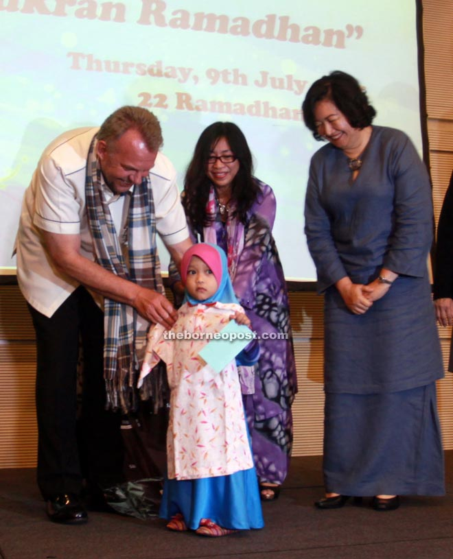 Torstein (left) and SEB chief of corporate services Aisah Eden (right) present Duit Raya to the children of Rumah Amal Nur Murni during the Ramadhan Iftar with the media at BCCK. — Photo by Jeffrey Mustapa