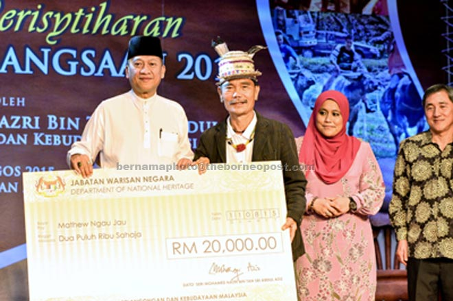 Nazri presents a cheque for the consolation prize to Ngau (second left) at the proclamation of National Heritage 2015 at Muzium Negara yesterday. — Bernama photo