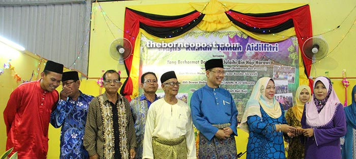 Julaihi's wife Datin Saadiah Buji Saadiah (third right) presents aid from the Sarawak Wives of Ministers and Assistant Ministers Welfare Association (Sabati) to a recipient. Julaihi is on her right.
