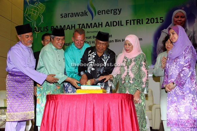 Adenan (fourth from left) cutting a 'pulut kuning' with (from left) Asfia, Awang Tengah, Sjotveit and Jamilah. — Photo by Chimon Upon