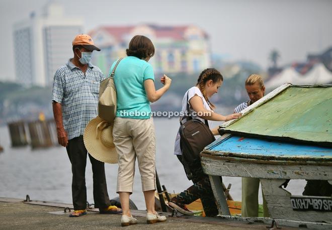 A 'perahu tambang' operator, wearing a mask, waits patiently as tourists board his boat at Pangkalan Sapi in Petra Jaya, Kuching, yesterday. Haze has returned, and the API reading in Kuching was 103 as of 2pm yesterday. — Photo by Muhammad Rais Sanusi