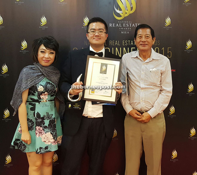 Wong (centre) poses with his award together with his mentor, Hii (right) and wife Emily Loo.