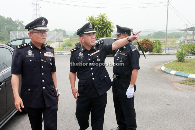 Ng (right) points at something as he greets Chai on his arrival at Padawan district police headquarters yesterday.