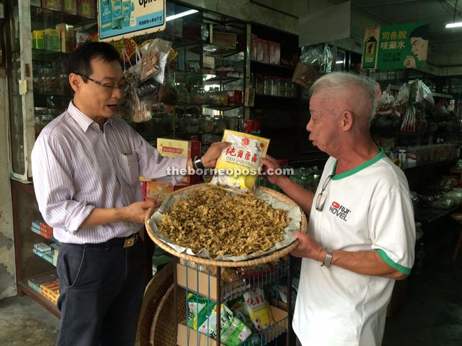 Trader Peter Wong (right) tells Kiang Chiok about the efficacy of his herbal products.