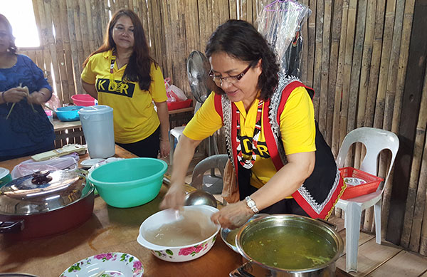 Candy Nyomui preparing linut  (glue-like sago paste).