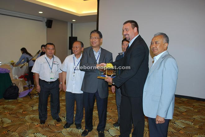 Talling (second right) receives a souvenir from Julaihi for his briefing on project implementation and employment opportunities.