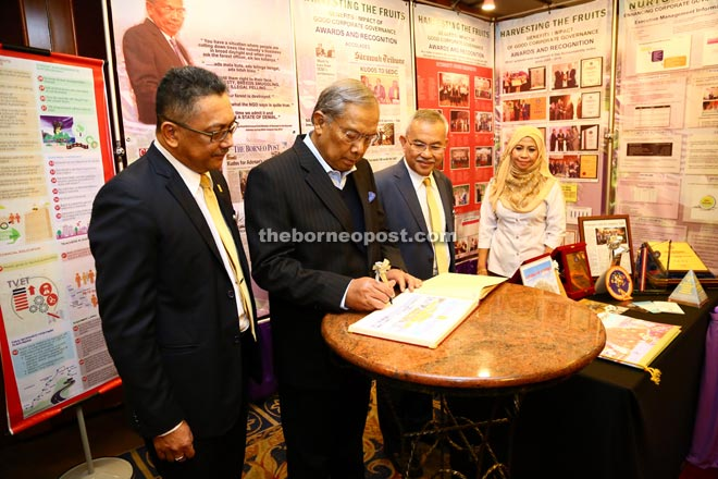 Adenan, flanked by Soedirman on his right and Talib, signing the visitor's book when he visited an exhibition by SEDC.