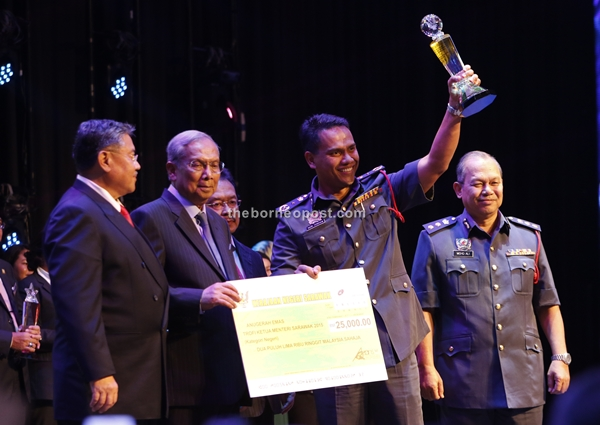 State Fire and Rescue Department director Nor Hisham Mohammad raises the Chief Minister trophy to celebrate the agency's first placing in the state category of the State Civil Service Quality Award. At second left is Adenan presenting the RM15,000 mock-cheque. Also seen (from left) are Morshidi, Yahaya (partly hidden) and state Fire and Rescue deputy director Mohd Alid Bahudin (right). - Photo by Chimon Upon