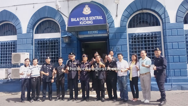 Pui (sixth right), Ismail (sixth left) and others giving the thumbs-up to cooperation between the community and the police after the dialogue.