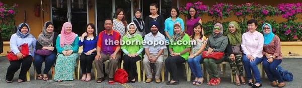 Siti (seated sixth left) with former teachersbehind the school.