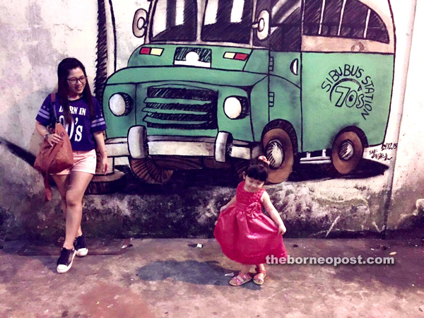 Amanda and her niece enjoy their time at the site of the nostalgic green-and-white bus wall painting at Blacksmith Road.