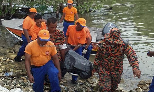Search and rescue personnel carrying the body of Ng ashore. — Bernama photo