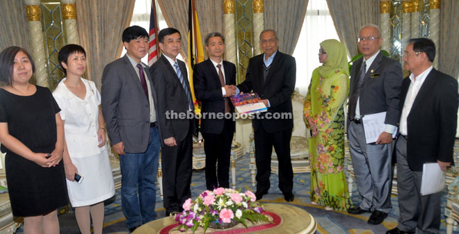 Wu (fifth from left) presents a memento to Adenan during the courtesy call.