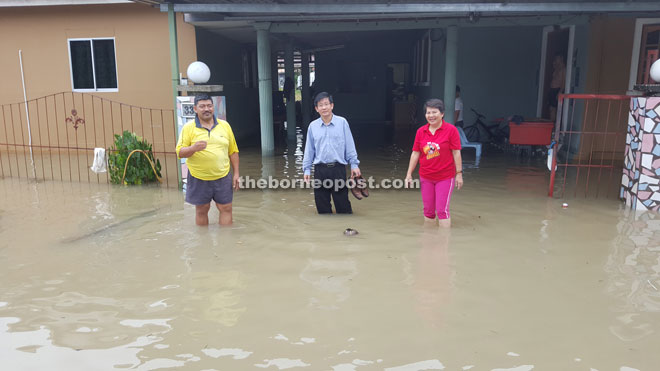 Tan (centre) visits one of the houses affected by the flash floods in Kuching.
