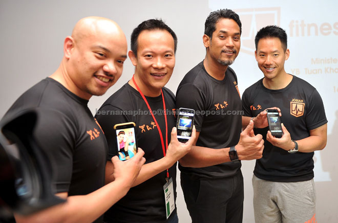 Khairy showing the new software applicatio, 'Fitness in My Pocket' after launching it in Kuala Lumpur. Also seen from left are personal trainer Ernie Tang, chief executive officer of eSolved MSC Sdn Bhd, Charles Tang and former national cyclist, Josiah Ng. 'Fitness in My Pocket' is the first Malaysian fitness training application featuring training plans by celebrity trainers like Josiah Ng, Ernie Tang and Laurel Stelzer. — Bernama photo