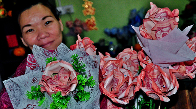 PRICY PETALS: An employee of a shop in Sibu shows roses fashioned from real RM10 notes. They were specially made for Valentine's Day today. Banknote flowers are still a popular trend among the townsfolk in celebrating the occasion, apart from the traditional fresh or plastic bouquets. — Photo by OTHMAN ISHAK