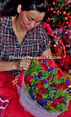 An employee prepares a more traditional Valentine's Day bouquet of fresh flowers.