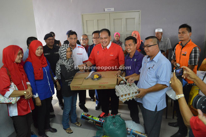 Samsudin (middle) presenting contribution to one of the fire victims.