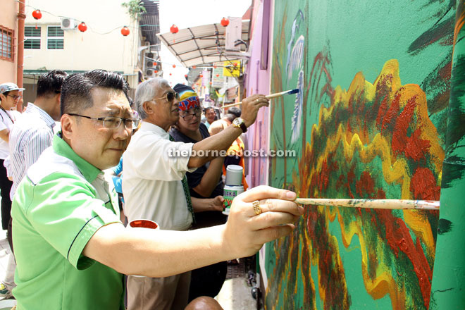 (From left) Wee, Abdul Wahap and Pearmain putting their personal touch on a wall of Kai Joo Lane. —  Photos by Chimon Upon.