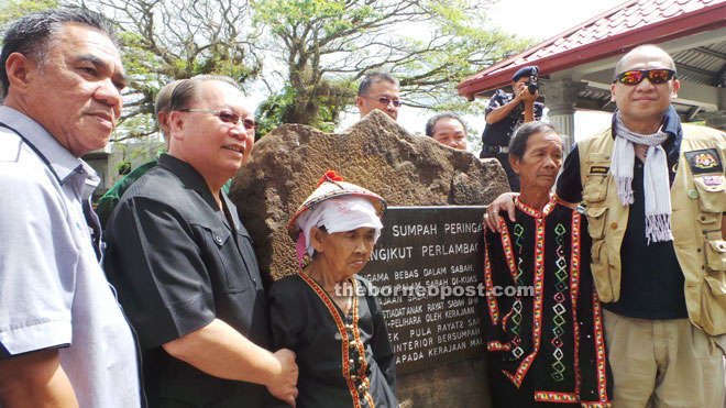 Nazri (right) with Pairin (second left) and Yusop (left) taking photograph with two Bobolians in front of the Oath Stone.