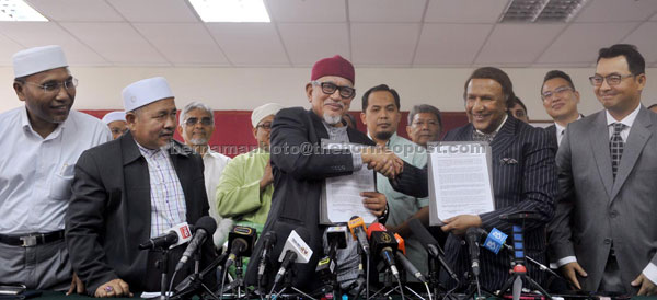 Abdul Hadi (centre) shaking hands with Abdul Kadir marking the establishment of a pact between both parties at the media conference in Kuala Lumpur yesterday. — Bernama photo