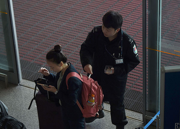 A security guard swipes a woman to check for explosives, at an entrance to the airport in Beijing. — AFP photo