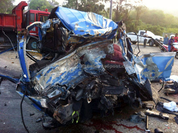 The badly damaged van in the crash that killed seven and injured two more. — Bernama photo