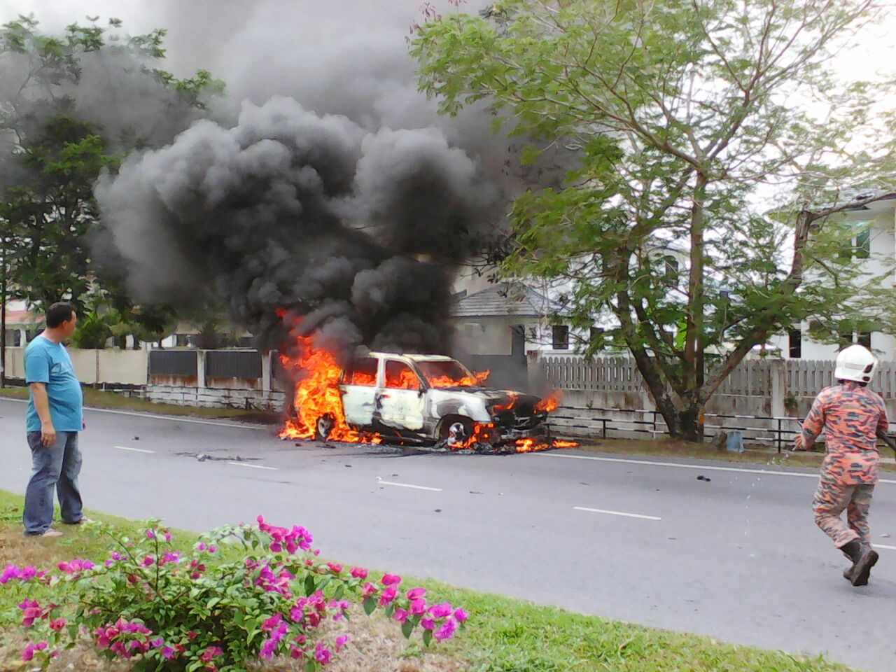 The car is seen ablaze at the roadside.