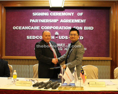 Loh (right) is seen during a photo call with Sedcotech-uds-i director Stuart Johnstone.