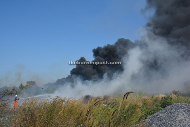A firefighter puts out the fire at the rubbish dump site near Taman RBA in Lutong Baru.