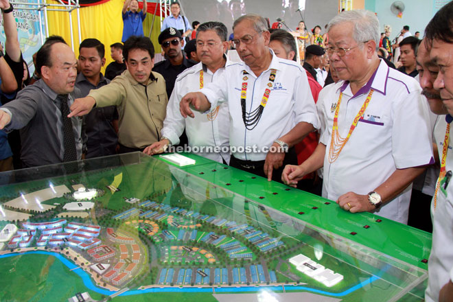 Adenan (centre) discusses the project with Morshidi (on his right) and Manyin (on his left) as they look at the development model. — Photo by Chimon Upon