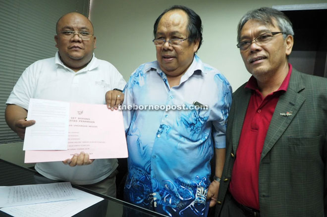 Anek (centre) and Louis holding a nomination form. Elli is on the right.