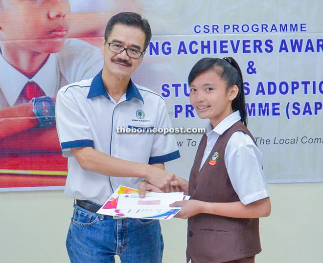 Wong hands over the incentive to a girl, who is part of the group's 'Young Achievers Award' recipients.