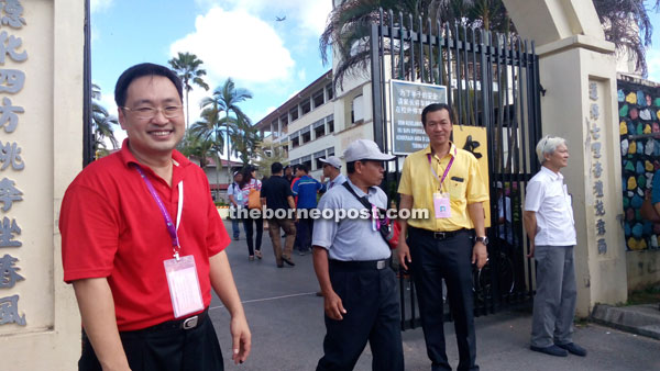 POLLING DAY HELLO: BN-SUPP Wilfred Yap (second right) and DAP Chong Chieng Jen (left) greeting voters for Kota Sentosa constituency at SRB Sam Hap Hin yesterday.