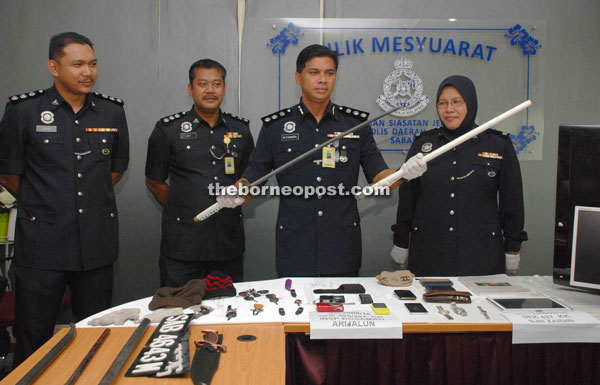 Chandra (second right) showing a samurai sword and other items that were seized from the suspects.
