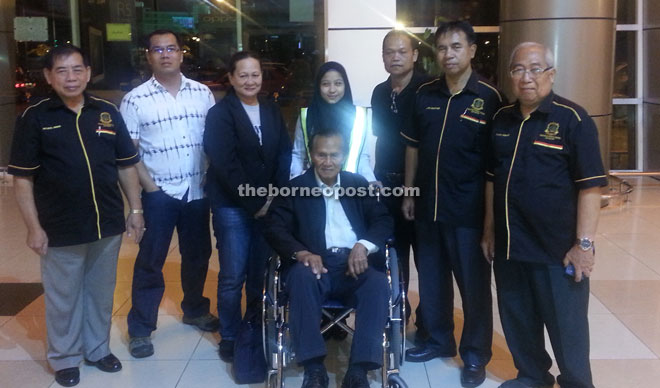 Awang on a wheel chair poses with PVTKR members at Kuching International Airport.