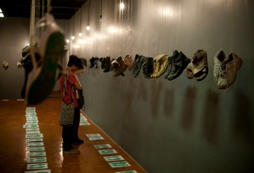"""People look at the shoes from the family members of missing people with messages printed on their soles at the """"Casa de la Memoria Indomita"""" museum in Mexico City on May 9, 2016, by Pauline De Deus 