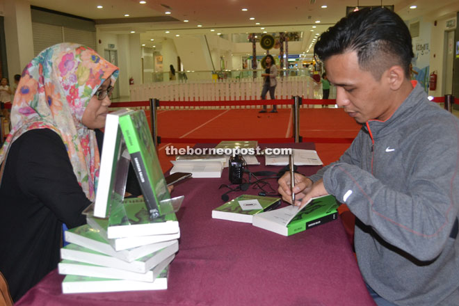Sahidzan (right) signing a copy of his book during the meet and greet session.