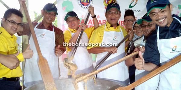 Abang Johari (third left) stirring the pot of bubur lambuk, flanked by Dr Abdul Rahman (fourth left), Abdul Karim and others. — Photo by Jeffery Mostapa