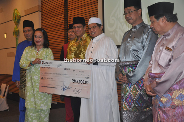 Abang Johari (third right) presenting the donation to KDJA vice president Jacqueline David. Also seen are Abdul Karim (second right) and Dr Abdul Rahman (fourth left).