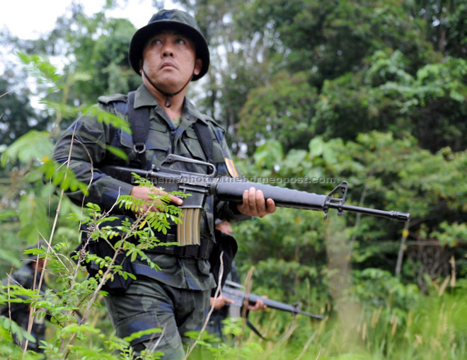 A General Operations Force (GOF) member from the 11th Battalion in Batu Kawah conducts a routine patrol along the checkpoint boundary in Telok Melano, Sematan which shares the border with West Kalimantan, Indonesia. — Bernama photo