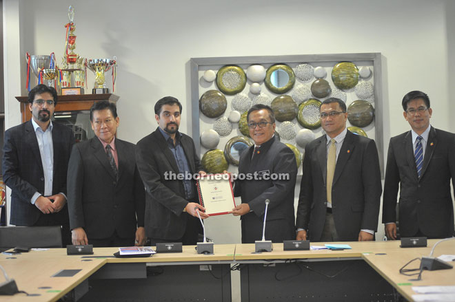 Kadim (third right) exchanges MoU documents with Enayat after the signing as others look on.